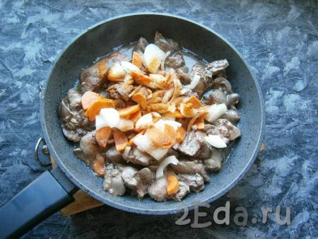 Обжарить сердечки с печенью на растительном масле, прикрыв сковороду крышкой, на достаточно сильном огне, периодически перемешивая, в течение минут 5. Затем добавить нарезанные лук с морковью, соль, перец и приправу для курицы.
