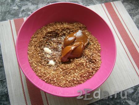 Печенье с орехами пересыпать в миску, влить растопленное сливочное масло, добавить варёную сгущенку.