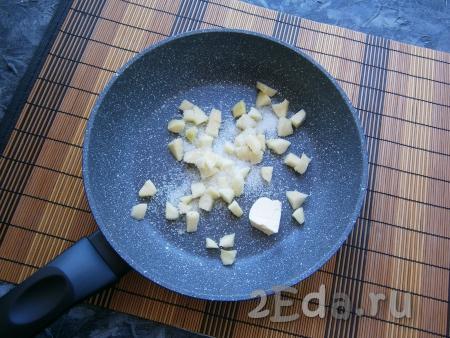 В сковороду выложить кусочек сливочного масла, добавить очищенное от кожуры и семян, нарезанное небольшими кубиками яблоко, всыпать сахар и ванильный сахар.