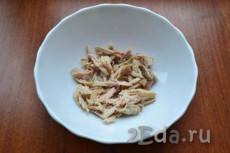 Вареное куриное мясо нарезать или разобрать на волокна.