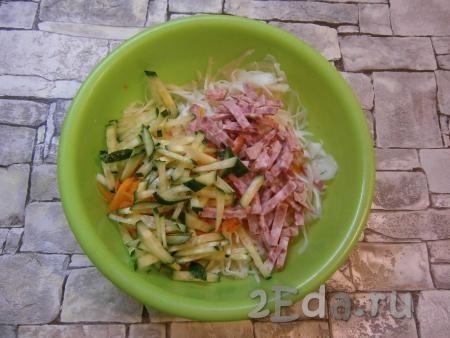 Тоненькими брусочками или соломкой нарезать огурец и колбасу, добавить их к капусте с морковью.