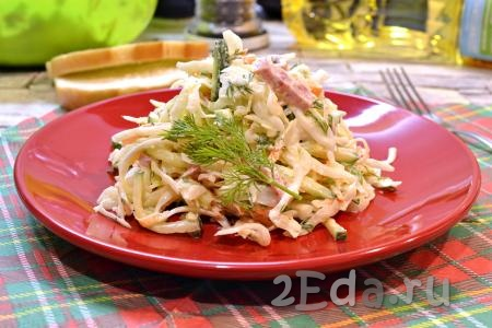 Выложить свежий и вкусный салат из капусты, приготовленный с копченой колбасой и огурцами, в салатник и сразу подать к столу.